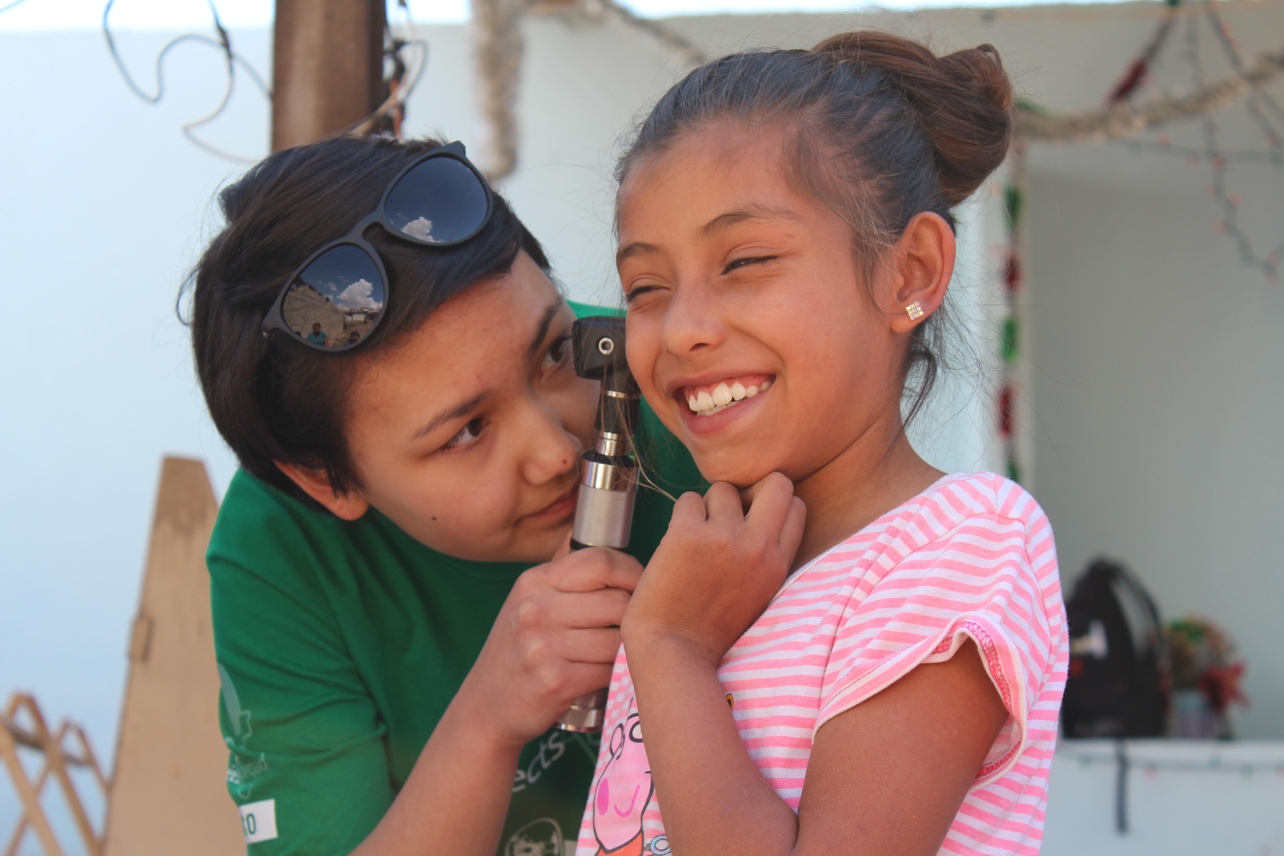 Medical Intern examines a young patients ear during a Medical Community Outreach Day in Mexico.